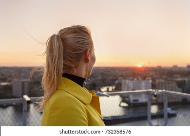Attractive young woman against the background of Amsterdam's cityscape in the sunset