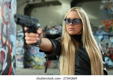 Attractive young woman aiming a gun.