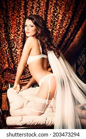 Attractive young woman alluring in sexual white lingerie and bridal veil.