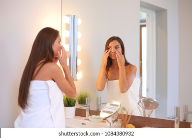Attractive young woman applying cream on her Face