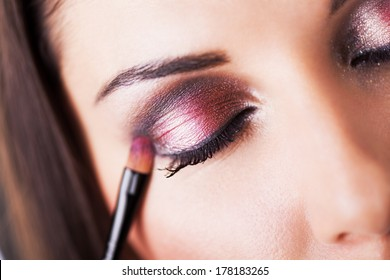 Attractive young woman applying eyeshadow. Close-up.