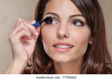 Attractive young woman applying mascara on her eyelashes