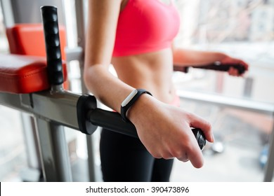 Attractive young woman athlete with fitness tracker on hand working out in gym