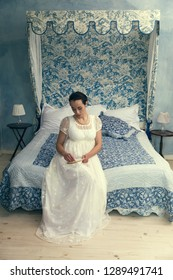 Attractive young woman in authentic regency dress sitting on an antique bed
