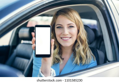 Attractive young woman in auto shows smartphone with blank screen.