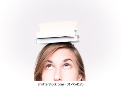 Attractive young woman balancing a book on her head White Background