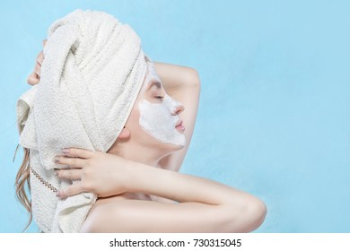 Attractive Young Woman with beautiful clean skin. White mask. Beauty treatments and cosmetology spa therapy. Blue background