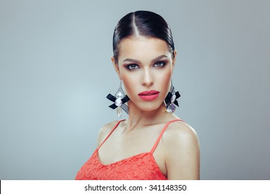 Attractive young woman with beautiful earrings posing in a studio