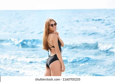 Attractive young woman in beautiful one-piece swimsuit on beach