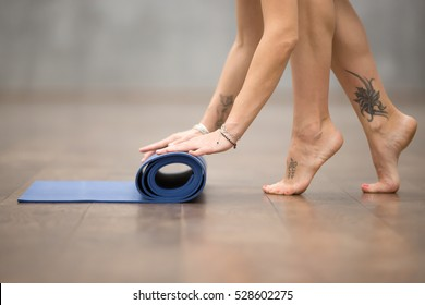 "Attractive young woman with beautiful tattoo on her foot meaning ""Wild kitty"" folding blue yoga or fitness mat after working out at home or in club. Close up of foot. Healthy life concept"