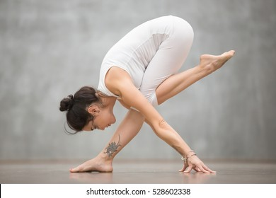 Attractive young woman with beautiful tattoo working out against grey wall, doing yoga, pilates balancing exercise. Full length