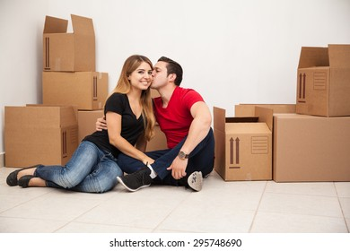 Attractive young woman being kissed in the cheek while moving into their new apartment