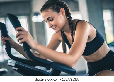 Attractive young woman biking in the gym, exercising legs doing cardio workout cycling bikes.