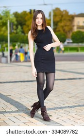 Attractive young woman in black dress posing outdoors