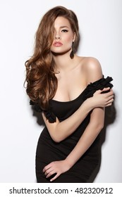 Attractive young woman in a black dress with a plunging neckline. Stylish girl model.