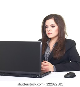 Attractive young woman in black jacket sitting at the table and working on a laptop. Isolated on white background