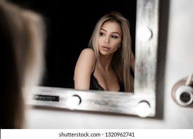 Attractive young woman blond with sexy lips with beautiful eyes in a black elegant lace bra sits in a dark room near  a white wooden mirror with lamps in a bedroom. Pretty face girl