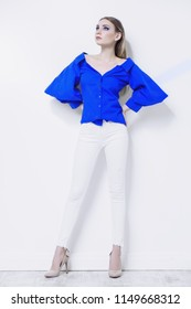 Attractive young woman in a blue blouse and white pants stands by a white wall. Beauty, fashion concept. Full length portrait.