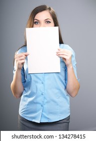 Attractive young woman in a blue shirt. Woman holds a poster and covers her face. On a gray background