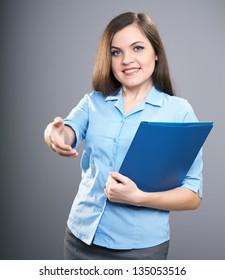 Attractive young woman in a blue shirt. Woman holds a blue folder and give a hand to shake. On a gray background