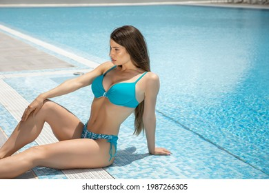 Attractive young woman in blue swimsuit relaxing by the swimming pool
