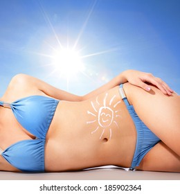 Attractive young woman body at the beach with sun shaped cream (sun block or sunscreen lotion ) over skin