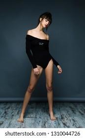 attractive young woman in bodysuit posing in studio