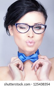 Attractive young woman with a bowtie kissing and winking