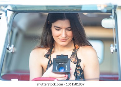 attractive young woman with camera classic, retro or vintage  behind the car glasses.concept of lifestyle photographer woman in hippie van