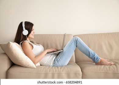 Attractive young woman in casual clothes and headphones lying on sofa and using laptop. Smiling teen girl listens and buying music in web store, watching online video, playing computer games at home