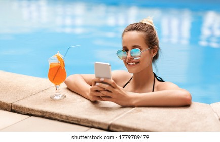 Attractive young woman with cellphone chatting online in swimming pool outside, panorama