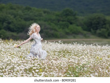 Attractive young woman with chamomile wreath running through the chamomile field. Blonde outdoors