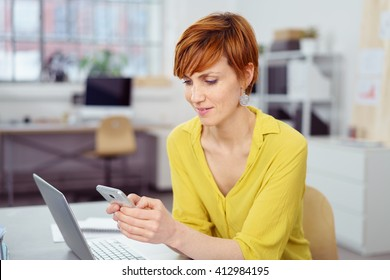 Attractive young woman checking her text messages on her mobile phone with a serious expression as she sits at her desk in the office