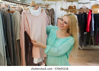 Attractive young woman choosing cloths in shop
