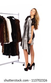 Attractive young woman choosing a fur coat from the hanger on white background