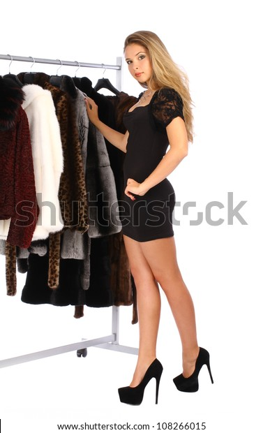 Attractive young woman choosing a fur coat from the hanger