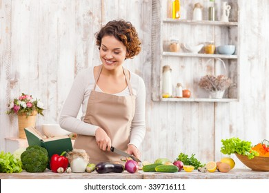 Attractive young woman is chopping vegetables in the kitchen. She is standing and reading a recipe from the book. The lady is cooking and smiling