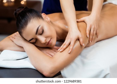 attractive young woman with closed eyes having massage in spa