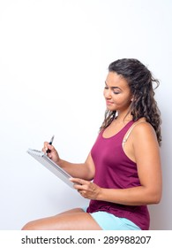 Attractive young woman of color holds a pen and clipboard