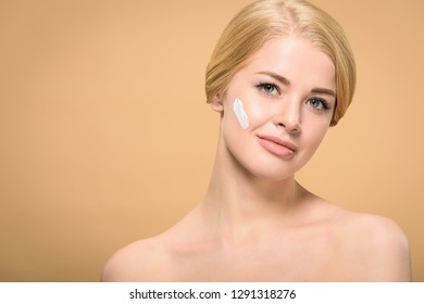 attractive young woman with cosmetic cream on face smiling at camera isolated on beige