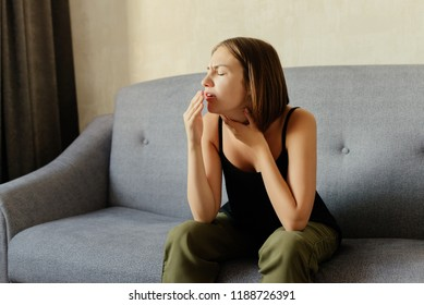 An attractive young woman coughs, covering her mouth with a hand, feeling cold and a sore throat, sitting on grey sofa, at home.