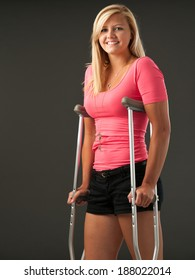 Attractive young woman with crutches. Studio shot with dark background.