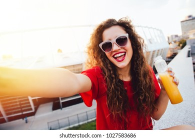 Attractive young woman with curly hair takes a selfie, posing and looking at camera, holds a bottle of fresh drink, outdoors.