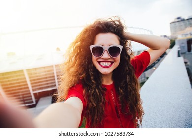 Attractive young woman with curly hair takes a selfie, posing and looking at camera, outdoors.