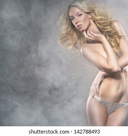 Attractive young woman is dancing striptease over smoky background