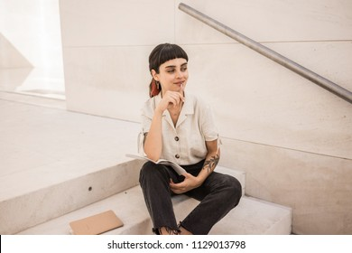 Attractive young woman with dark hair and smile sits on stairs of office or university and thinks about her notes in notebook looking to side. Girl wears black jeans and light blouse.