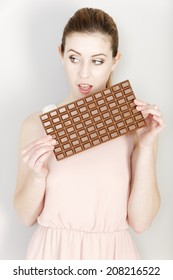 Attractive young woman deciding on whether to eat a piece of chocolate.
