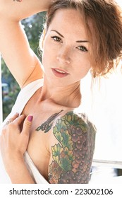 Attractive young woman displaying a colorful arm tattoo as she lowers the shoulder of her summer top