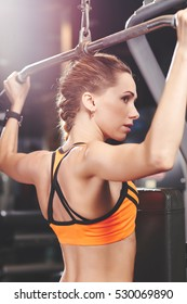 Attractive young woman doing exercise for back on lat machine