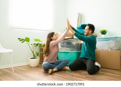 Attractive young woman doing a high five with her happy partner. Hispanic couple smiling and celebrating their moving day
